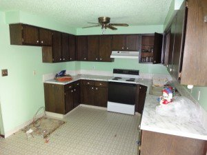 A kitchen, featuring lime green paint, older cabinets and no refrigerator.  Looks a little rough
