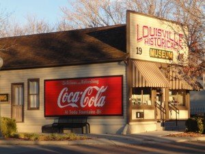 sun and shade dappled historic building with a bright red and white coca-cola mural
