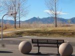 Two large spheres in the foreground, then a bench and a basketball court. In the background are the Rocky Mountains