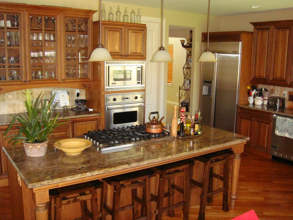 counter tops are highlighed in this gourmet kitchen island in foreground iwth slab granite