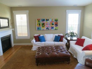 family room, bright accent pillows catch eye on white couches, art on wall is colorful but non threatening