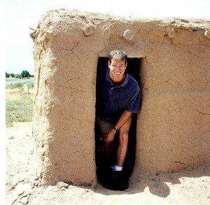 Realtor bob gordon emerging from a mud house