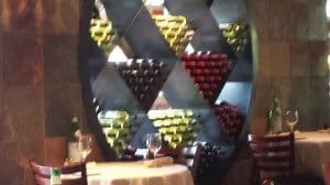Boulder Italian Dining hall carellis presents wine as art, with a large circle divided into triangles, each holding several bottles of wine.
