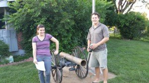 emily and ben in front of a cannon at a house for sale