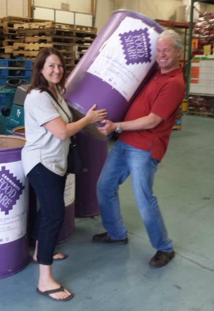 julie and realtor bob gordon at community food share with bob hoisting a barrel