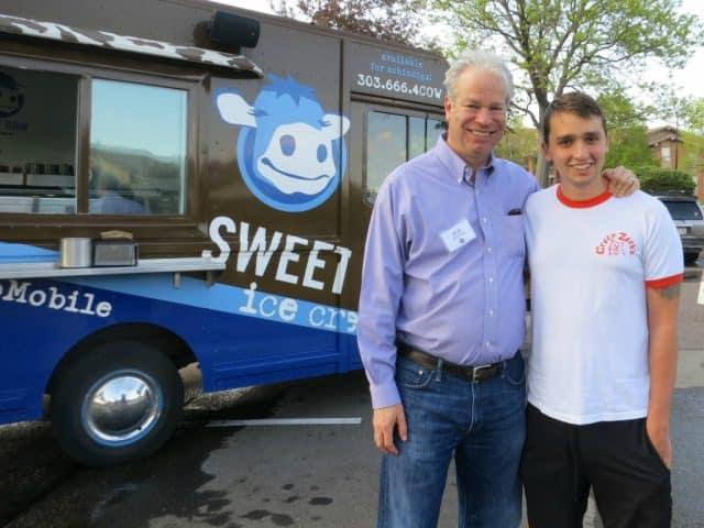 sweet cow truck, realtor bob gordon posing alongside son bear peterson-gordon at community food share event