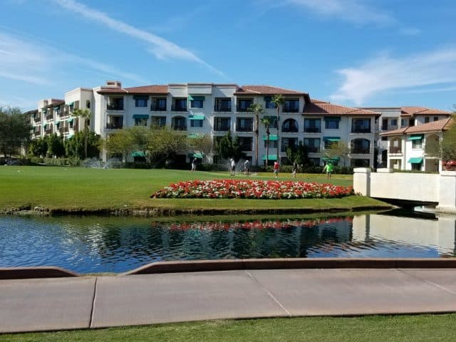 arizona grand resort with water feature in foreground, golfers and hotel rooms in background