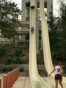 bob gordon going down a very tall water slide and screaming quite loudly