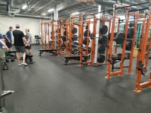 weight room at sport stable with a few people inadvertantly in frame.