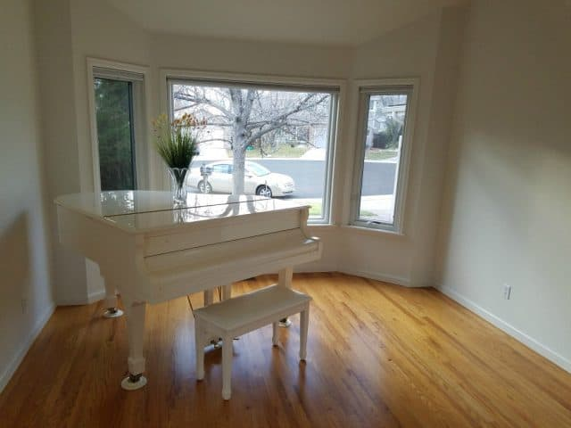 white baby grand piano in living room at 4566 pussy willow ct boulder co 80301