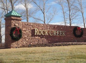 """A red brick wall with the words, """"Rock Creek"""" in gold and behind, a tall strand of trees"""