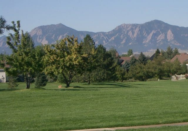 view of the flatirons in boulder colorado across a big field of park like grounds