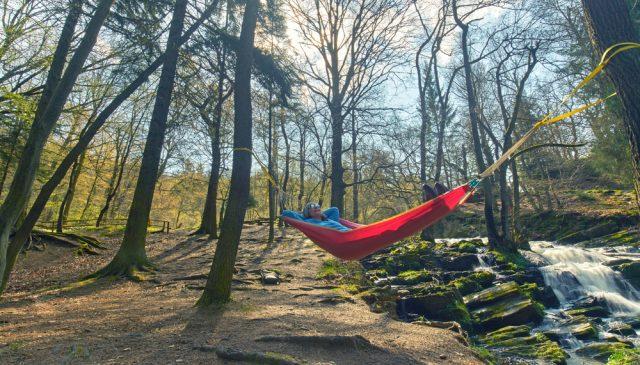 girl relaxing in hammock alongside boulder creek